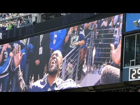Kam Chancellor visits & raises the 12th Man Flag.